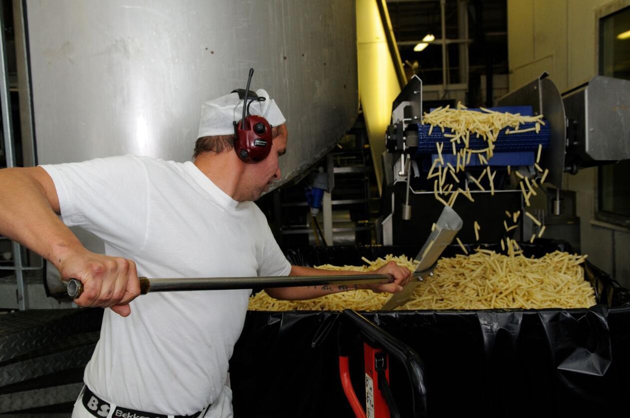 Her skyfler en medarbeider ved Hoff Potetindustri SA på Gjøvik pommes frites som skal pakkes i poser. Foto: Oliver Orskaug