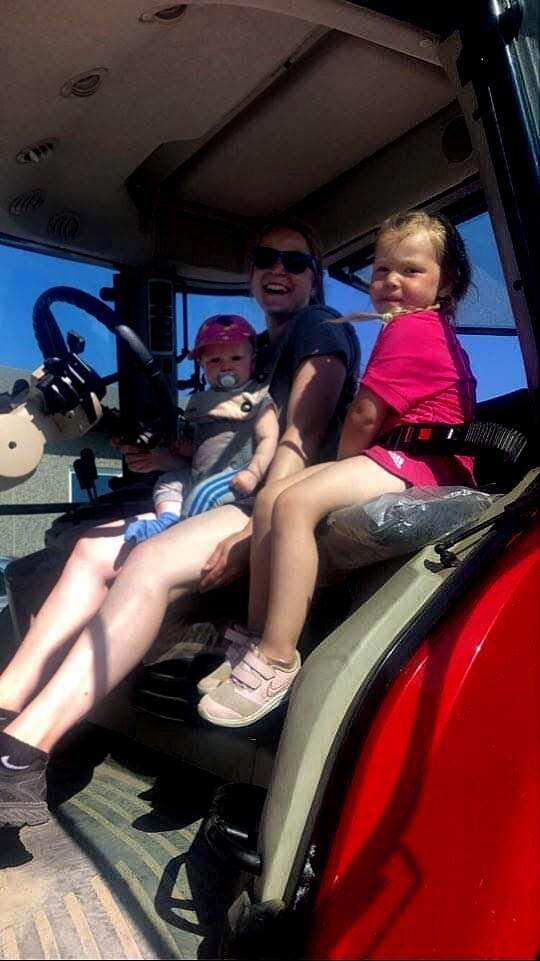 Monika Bratland i traktoren med barna: – Her var minsten ni måneder og vi måtte få inn høyet. Alle måtte være med, så det ble legging klokka ti om kvelden, sier hun. Foto: Privat