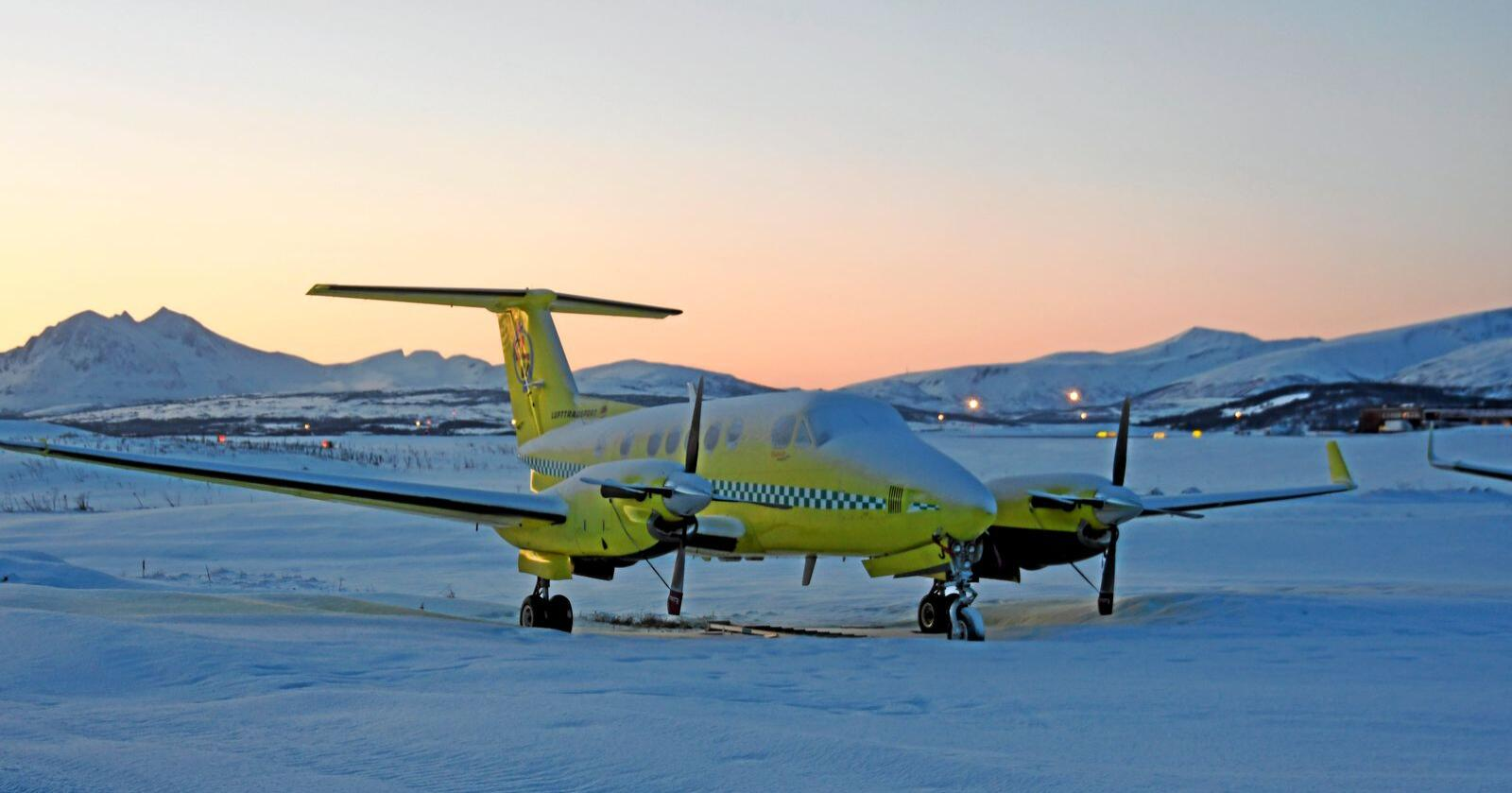 Bilde av ambulansefly i snøen utenfor flyplassen i Tromsø. Foto: Rune Stoltz Bertinussen / NTB scanpix