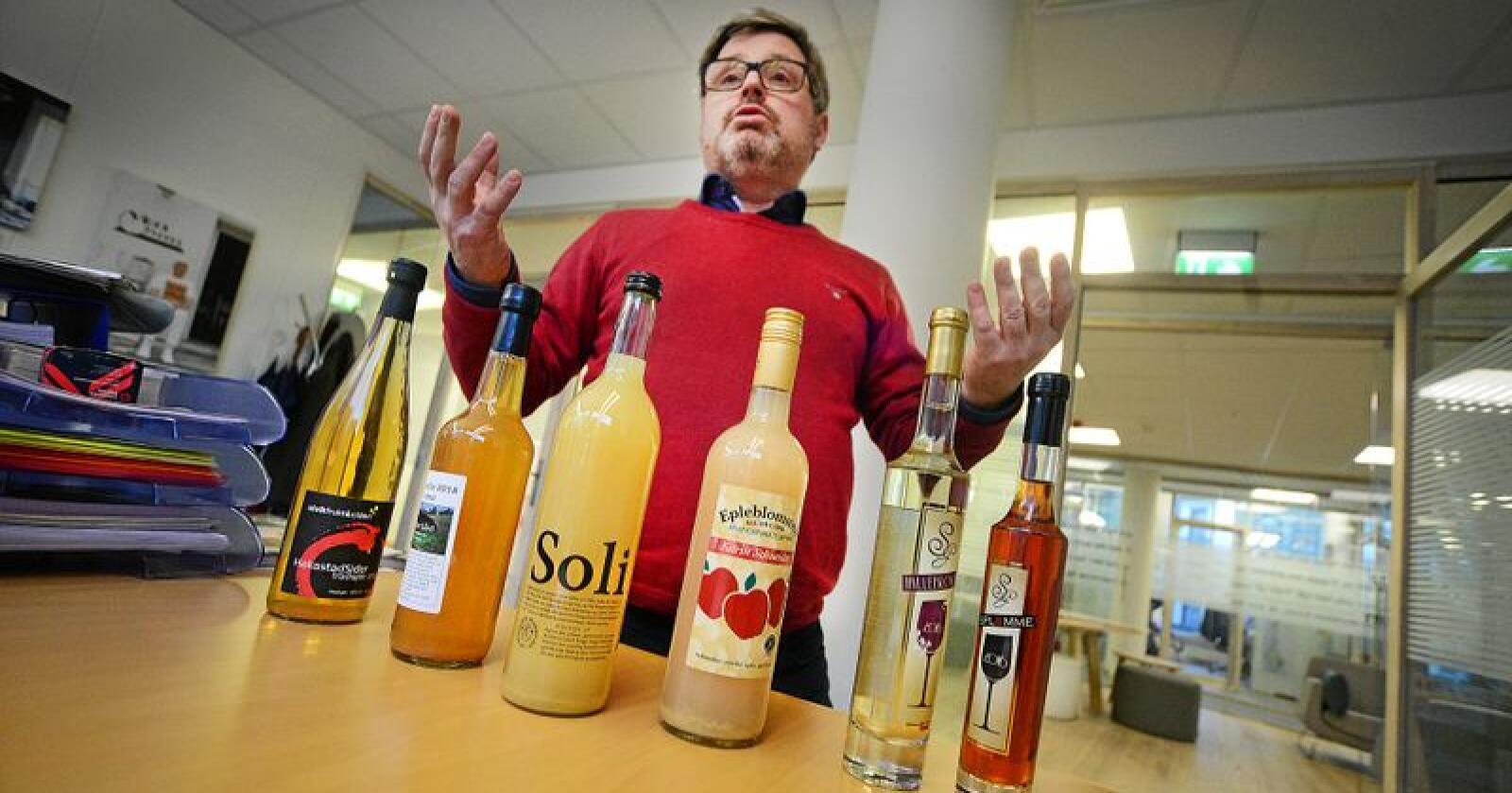 Bernt Bucher-Johannessen viser frem noen av produktene som skal være med i konkurransen om Norges beste eplemost, sider og fruktvin. Foto: Siri Juell Rasmussen
