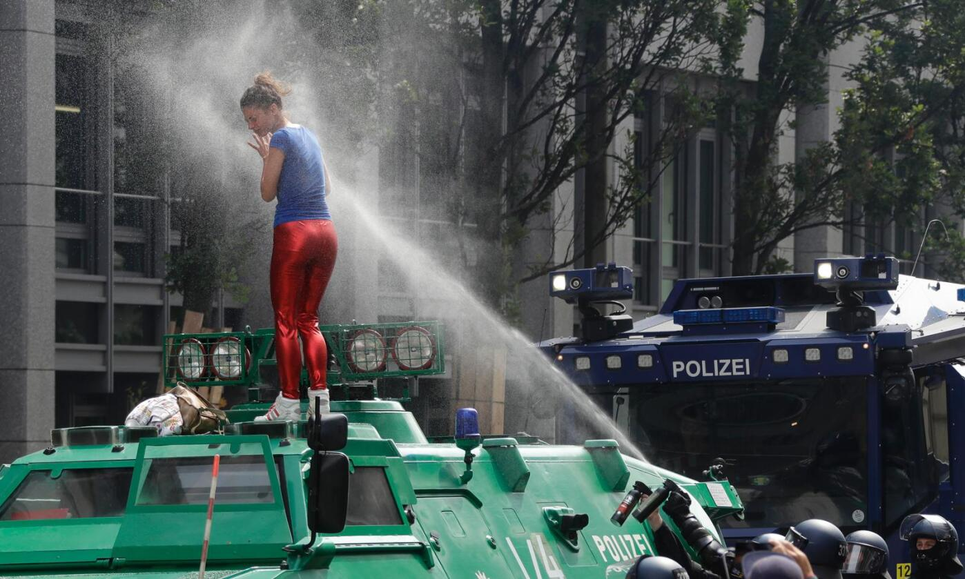 Pepperspray: En kvinne i røde bukser «åpnet» G20-toppmøtets første dag med å få en pepperspray-dusj etter å ha klatret opp på en pansret politibil. Så ble det bare verre. Foto: AP Photo / Matthias Schrader / NTB scanpix