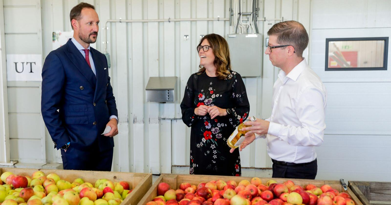Kronprins Haakon sammen med daglig leder Astrid Lier Rømuld og kvalitets- og utviklingssjef Lars Erik Pettersen ved Askim Frukt- og Bærpresseri. Foto: Berit Roald / NTB