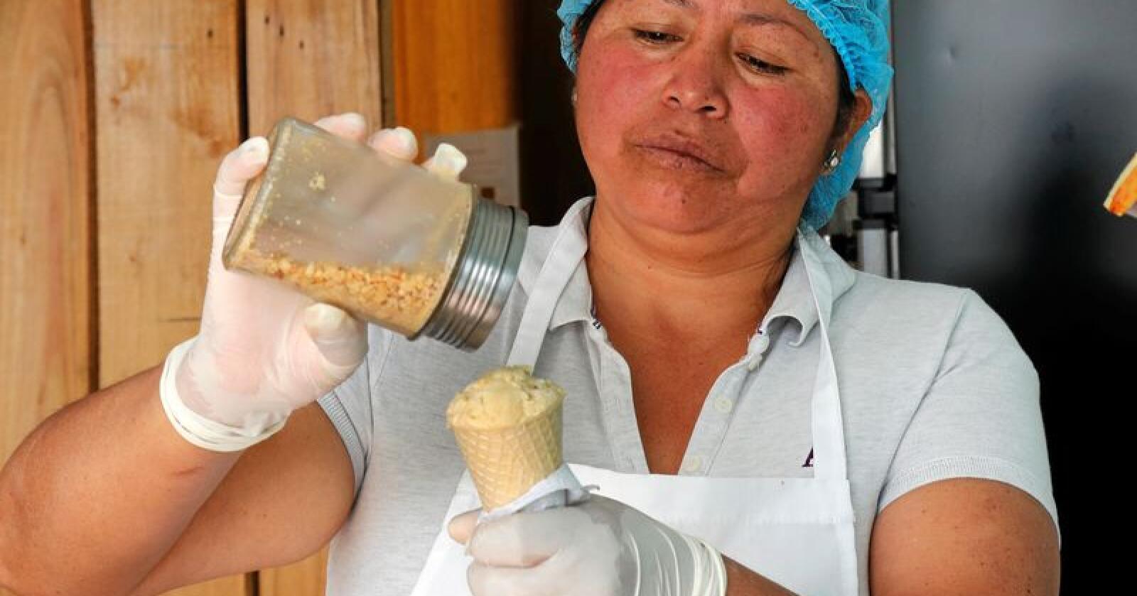 Maria del Carmen Pilapaña heller litt peanøtter på en kule is med marsvin-smak. Blant andre varianter hun byr på, er iskrem laget av sopp. Foto: Dolores Ochoa / AP / NTB Scanpix
