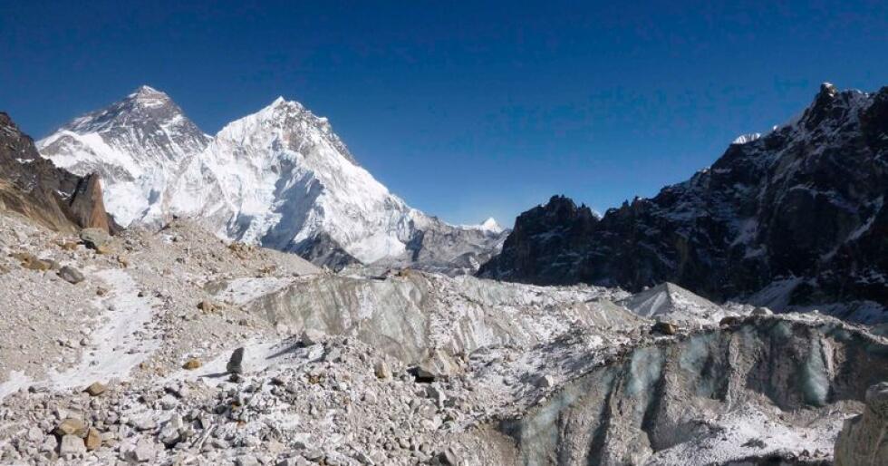Isbreen Changri Nup, delvis dekket av stein og grus. Breen ligger i Himalaya-fjellene i Nepal, og Mount Everest er synlig i bakgrunnen på bildet. Høyere temperaturer har ført til en kraftig økning i bresmeltingen i Himalaya. Foto: Joshua Maurer / AP / NTB scanpixklima