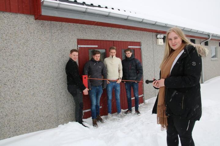 Leder dyra: Silje Østensen viser hvordan det mobile gjerdet kan trekkes ut ved fjøsdøra. Videre fra høyre Audun Murud, Eivind Thoresen, Emil Samuelshaug og Henrik Løkken.