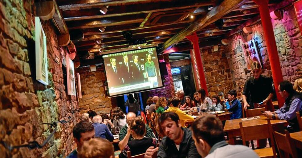 TV-debatt: Følger tv-debatten i restauranten. På skjermen fra venstre høyreleder Pablo Casado, statsminister Pedro Sanchez, sosialdemokratene, Albert Rivera, leder for «Borgerne» (lyseblått parti) og Pablo Iglesias, leder for Podemos Unidas («SV»). Vox-lederen var ikke med, fordi han ikke sitter i parlamentet.  Foto: Alvaro Barrientos/AP/NTB scanpix
