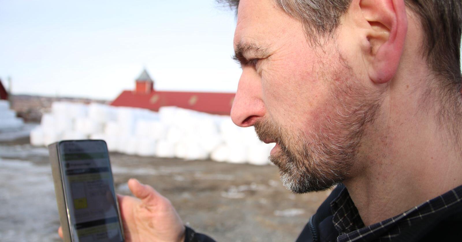 Her ser Christian Diskerud Meyer på mobilapp'en til Agrilogg, for å sjekke varelageret med grovfôr.