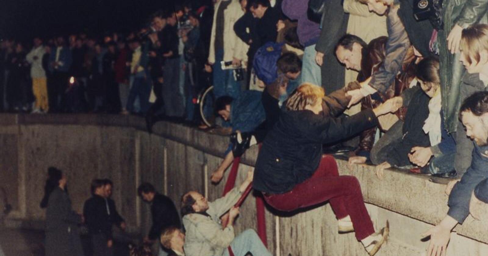 Innbyggere i Øst-Berlin får hjelp av folk fra vest til å klatre over Berlinmuren 10. november 1989. Foto: Jockel Finck / AP / NTB scanpix