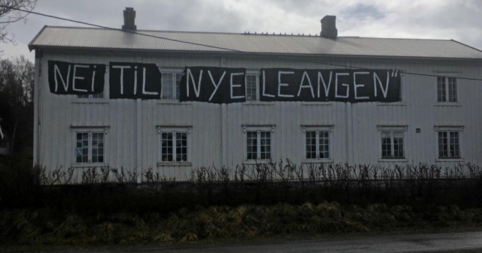 Randi Jacobsen har hengt opp et stort banner på våningshuset ut mot åkeren som Midt-Norge Travforbund ønsker å bygge trøndertravets nye storstue på. Foto: Randi Jacobsen