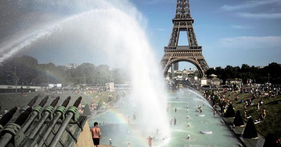 Mennesker i Paris brukte fontene ved Eiffeltårnet til å kjøle seg ned under hetebølgen i Europa i slutten av juni måned. Foto: Lewis Joly / AP / NTB scanpix