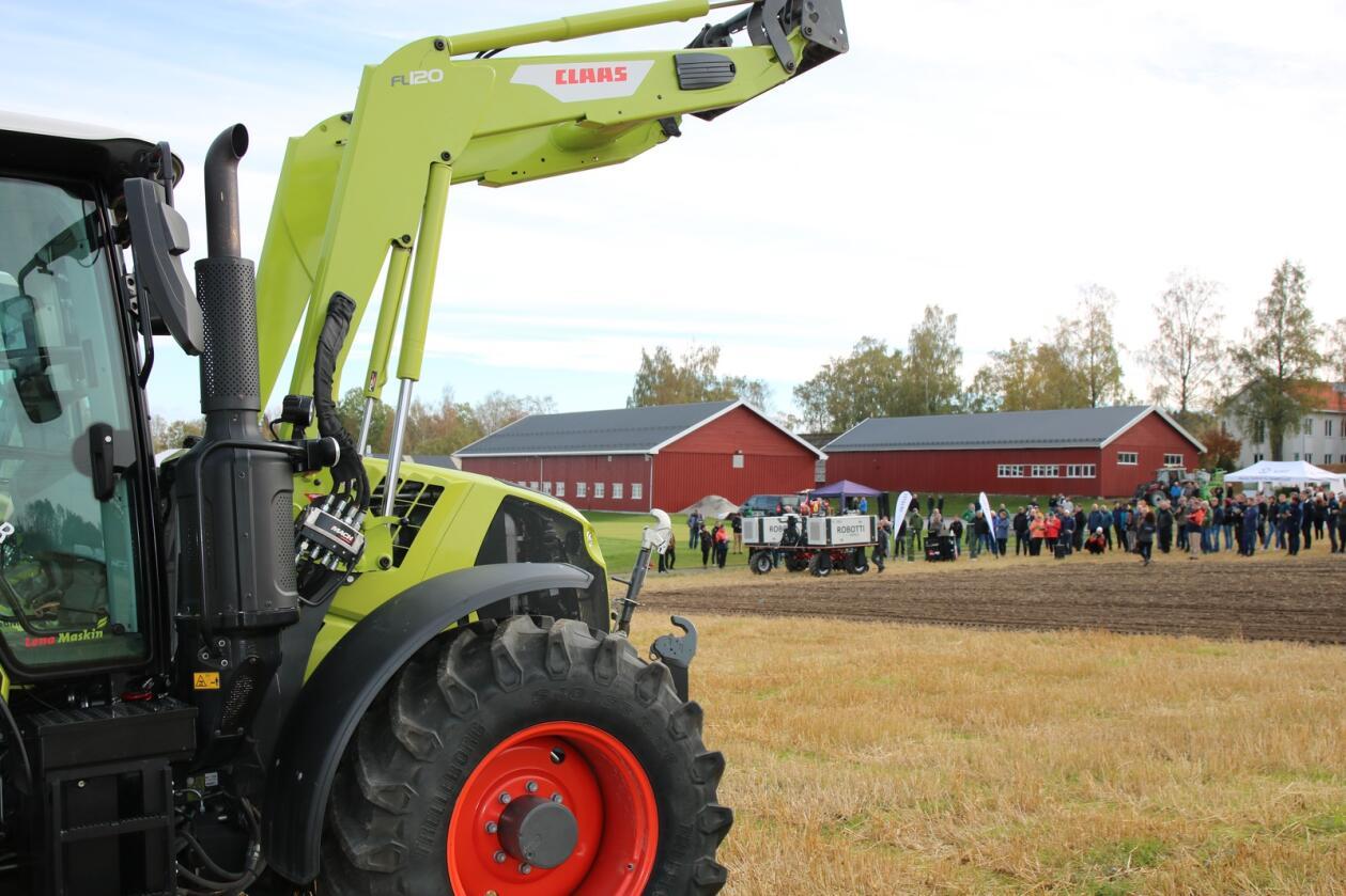 AUTOMATISERING: De tradisjonelle traktorene vil i fremtiden overlate flere og flere oppgaver i jordbruket til roboter. I bakgrunnen demonstrerer den danske roboten ROBOTTI hvordan den jobber på et jorde.