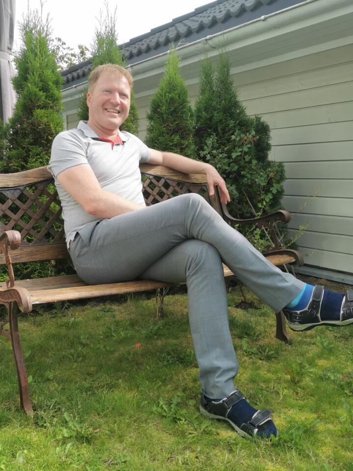 Etter en lang og tung vår kan Sigbjørn Gjelsvik (Sp) ta seg tiden til et smil i hagen på Sørum. Foto: Henrik Heldahl