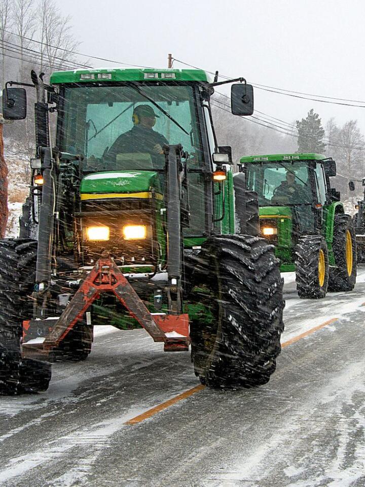 Lys i uværet: Tette snøbyger fra vest slår inn som et hvitt sceneteppe over riksveien i Skjåk – der plutselig lysene fra en diger karavane med traktorer bryter gjennom uværet fra fjellheimen. Alle foto: Bård Bårdløkken