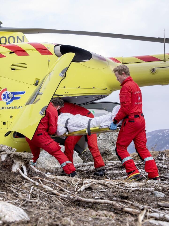 En pasient blir hentet ned etter skade ute i skogen. Foto: Norsk Luftambulanse.