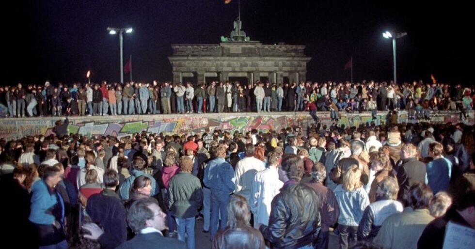 Berlinmurens fall: Tusenvis av mennesker krabbet opp på muren ved Brandenburger Tor i Vest-Berlin kvelden 9. november 1989, rett før grensa ble åpnet. Foto: Jørn H. Moen/SCANPIX