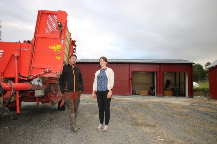 POTETBØNDER: Her står Sigurd og Eva ved potetopptakeren. I bakgrunnen er det nye potetlageret.