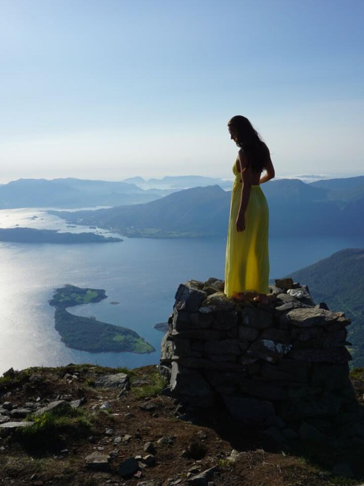 STORSLAGENT: Julie Bjanes synes finkjoler står godt til norsk natur, selv om enkelte rynker på nesen over at hun pynter seg til fjells. For ordens skyld: Kjolen ligger i sekken til hun har nådd toppen. Foto: Julie Bjanes