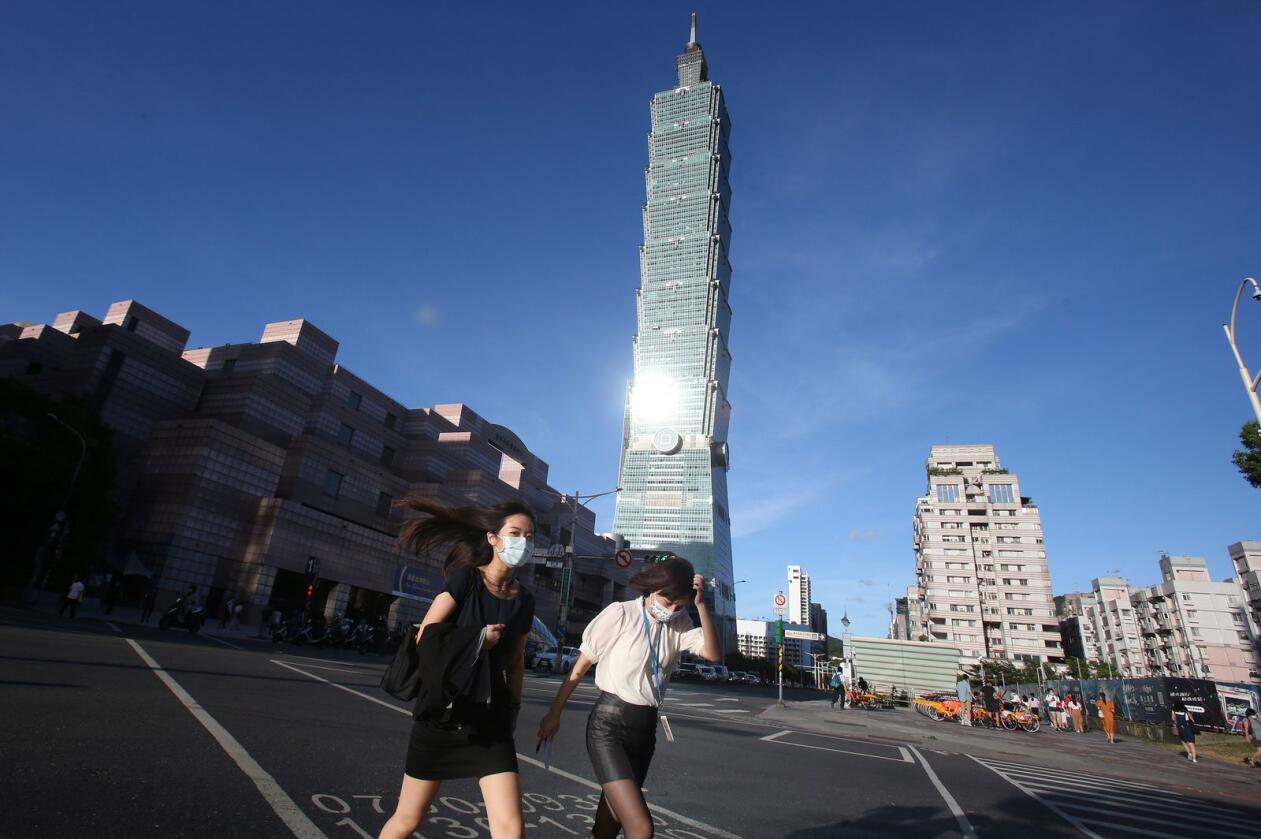 In front of the iconic Taipei 101 skyscraper, people cross an intersection wearing face masks to help protect against the spread of the coronavirus after the COVID-19 alert rose to level 3 in Taipei, Taiwan, Thursday, July 15, 2021. (AP Photo/Chiang Ying-ying)