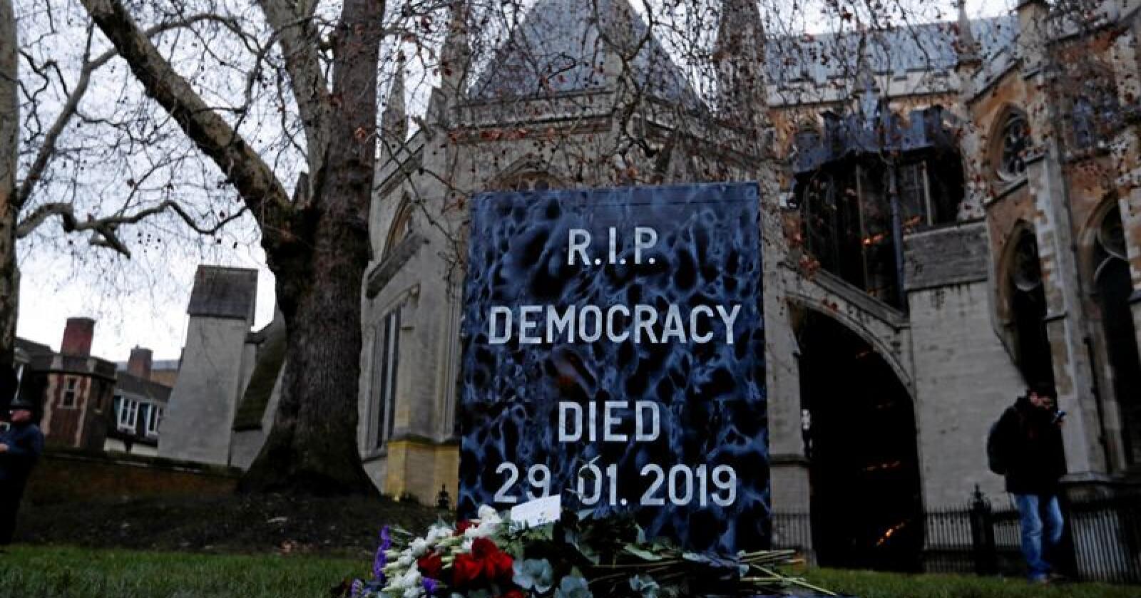 """""""Demokratiet døde 29. januar 2019"""" står det på denne """"gravsteinen"""" foran det britiske parlamentet. Steinen ble plassert av EU-motstandere. Foto: Alastair Grant / NTB Scanpix"""