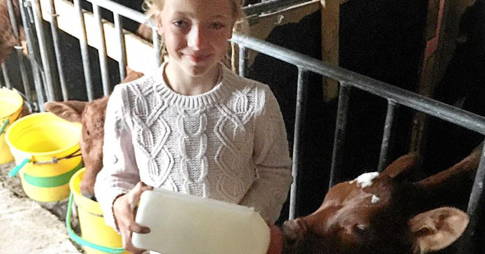 Sofie Richter gir mjølk til kalven, som vart oppkalla etter den vesle feriebudeia. Foto: Privat