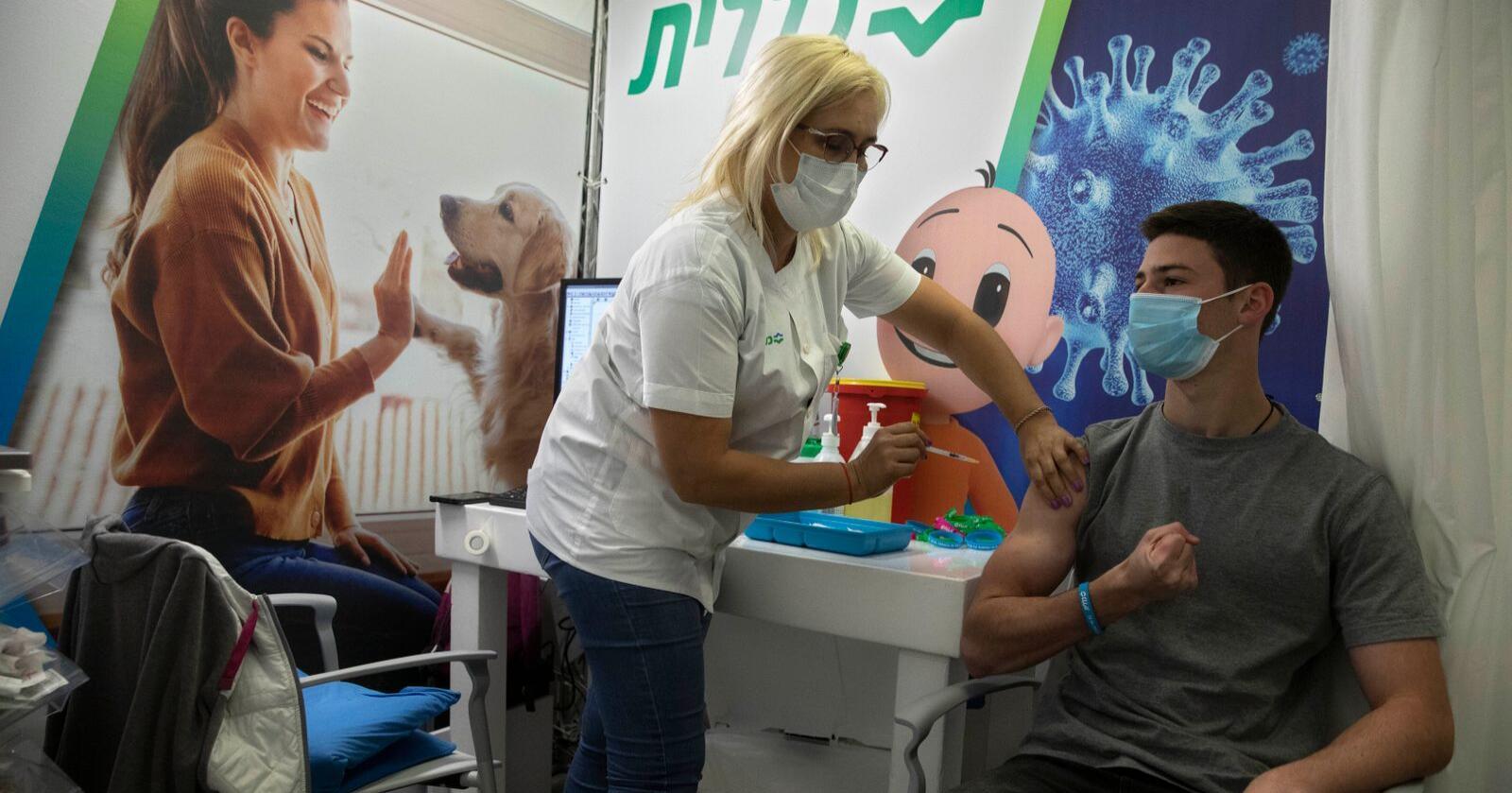 Her får en israelsk ungdom Pfizer-BioNTech-vaksinen på et vaksinesenter i Holon nær Tel Aviv.  Foto: AP Photo/Sebastian Scheiner