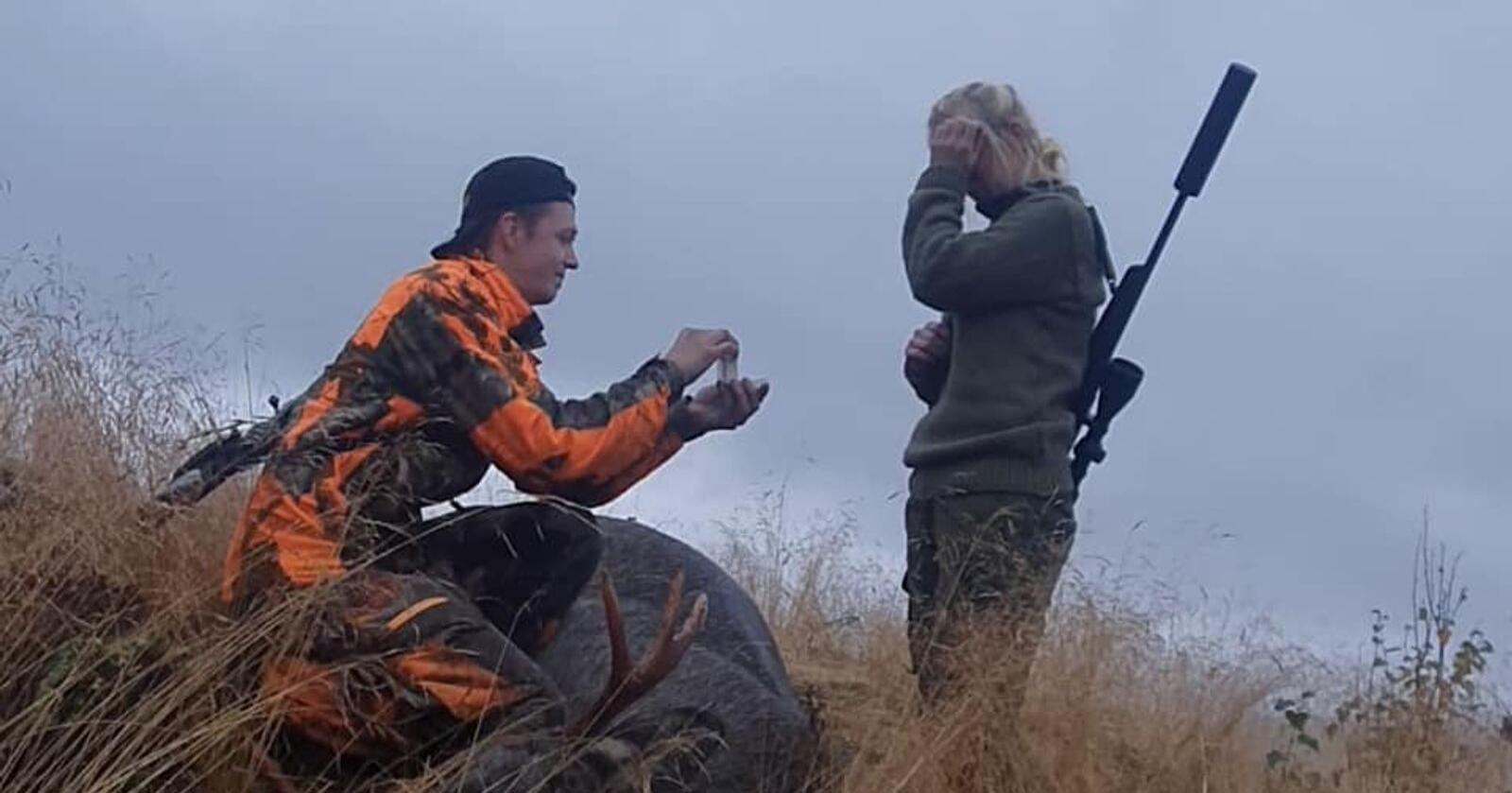Her frir Stian Edvin Tjolmen til kjæresten Cathrine Aasrum under helgas elgjakt. Mellom dem ligger elgoksen som Tjolmen felte bare kort tid før frieriet. Foto: Privat