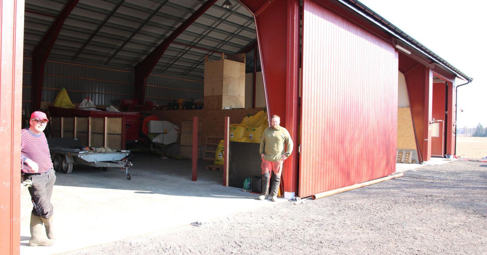 Erik Aarhus (t.v) og Emil har satt opp en ny driftsbygning med plantørke i to seksjoner, verksted og traktorgarasje. Halve garasjen kan enkelt gjøres om til kornlager. Foto: Knut Houge