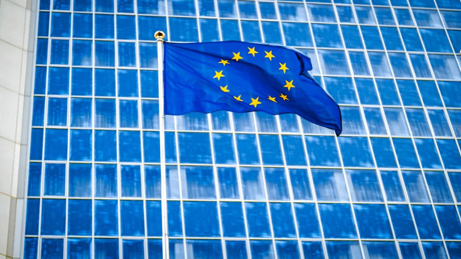 Photo of EU flag fluttering on wind against high business office building made of concerete and glass. Concept of ecenomics, development, government and politics