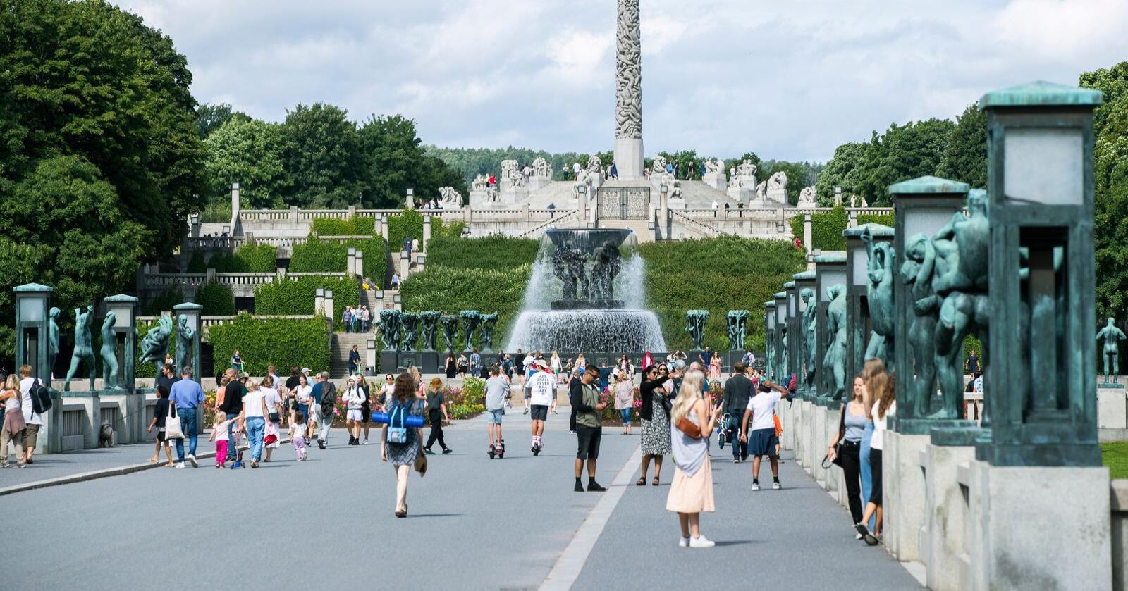 Turister kikker på skulpturene i Frognerparken i Oslo. Sommeren gikk bedre enn ventet for den norske reiselivsnæringen, men frykten er at høsten blir tung. Mandag kommer det mer krisehjelp. Foto: Berit Roald / NTB