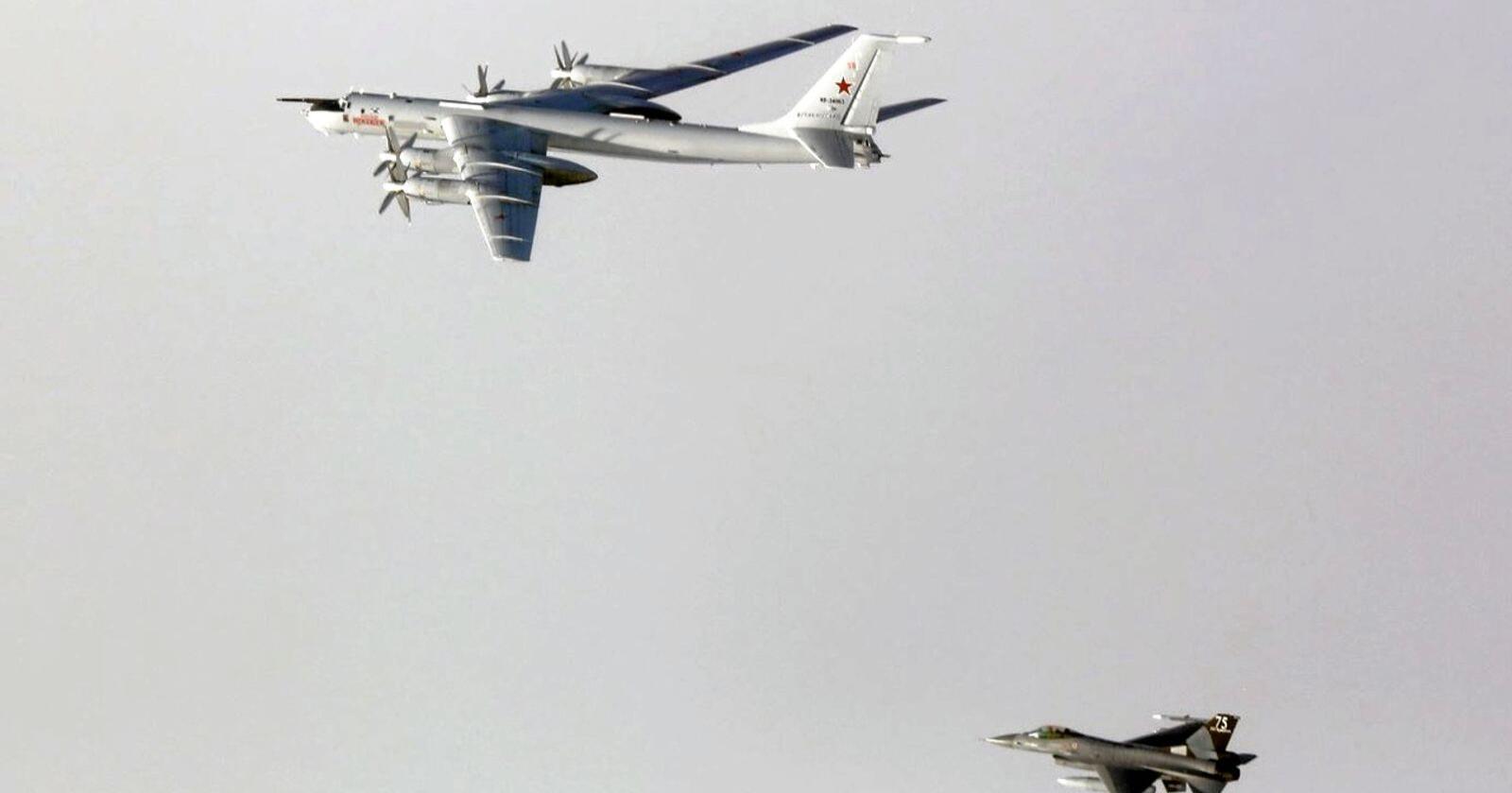 Et russisk strategisk bombefly med Nato-betegnelsen «Bear» følges av et norsk F-16 kampfly langs norskekysten, i mai 2020. Foto: FOH