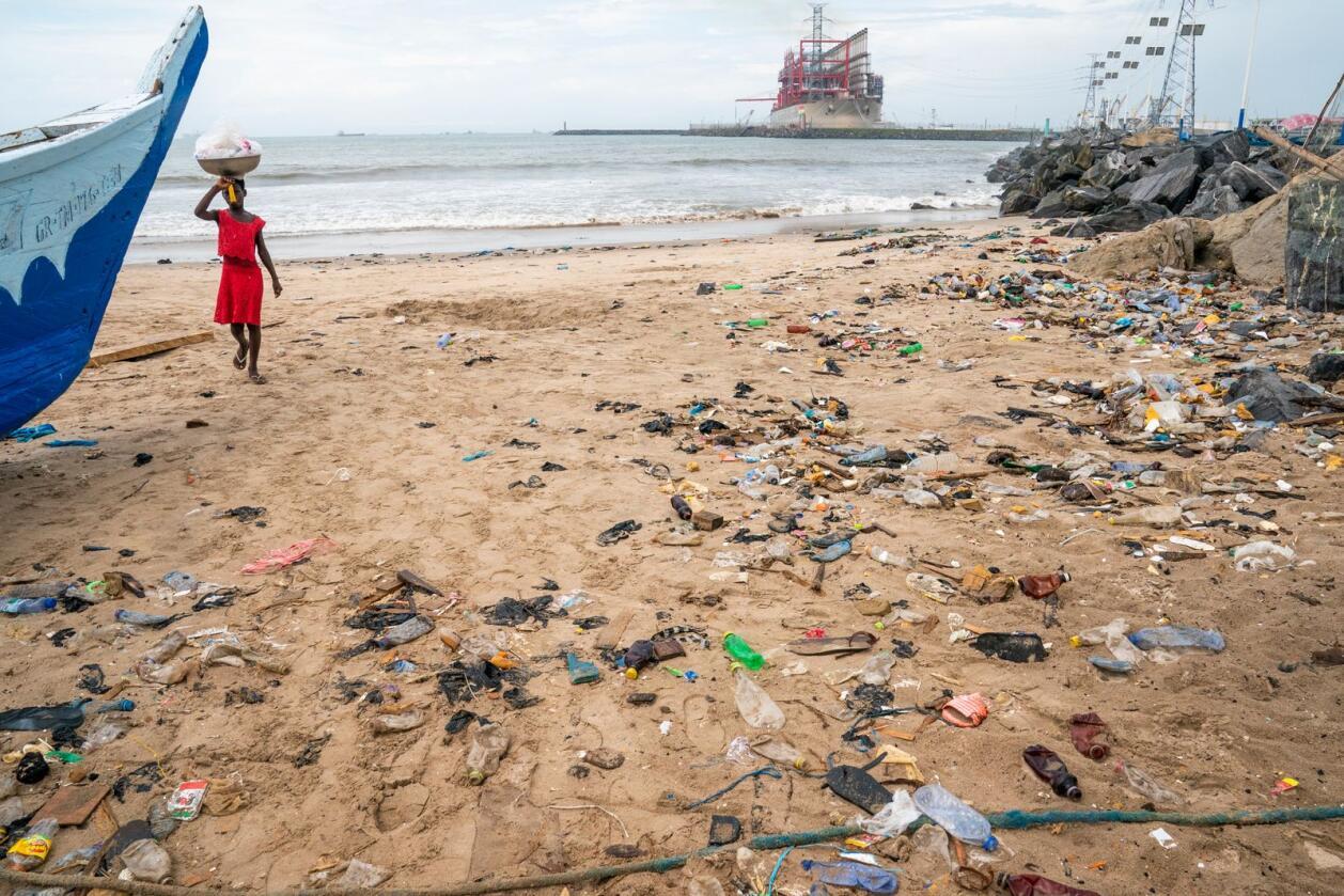 En jente går på en forsøplet strand i havnebyen Tema utenfor Accra i Ghana. Foto: Heiko Junge/NTB scanpix