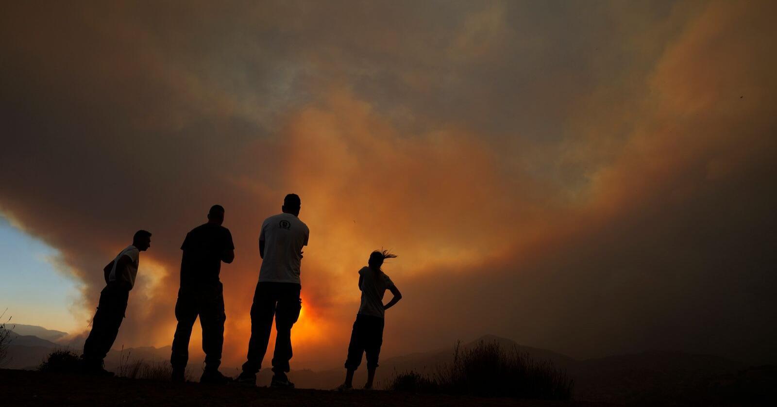Innbyggere ser på brannen som herjer i et fjellområde ved Larnaka. Foto Petros Karadjias / AP / NTB