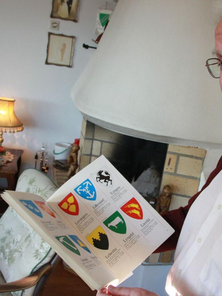 Heraldiker Tom Sverre Vadholm kan mye om kommunevåpen. Her viser han fram en bok med oversikt over alle de norske kommunevåpnene. Foto: Kjell Åsmund Sunde / NPK
