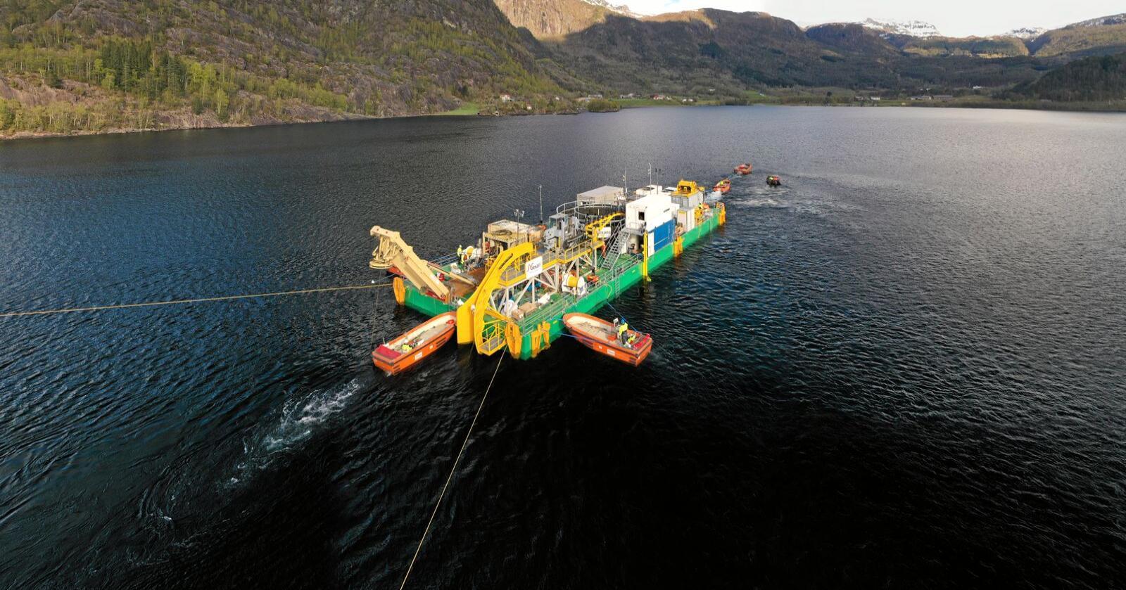 For å legge kabelen i krevende vanndybde på over 200 meter på dypeste i Suldalsvatnet brukes en spsesiallaga arbeidsplattform. Plattformen trekkes over vannet ved hjelp av arbeidsbåter. Foto: Statnett