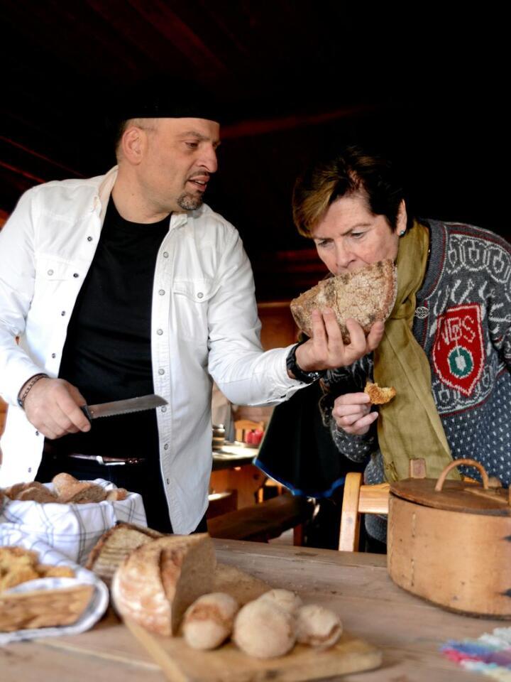 Baker Alexander Somalakis lar prosjektleder Merete Furuberg kjenne den deilig duften av nybakt brød av svedjerug . Foto: Mariann Tvete