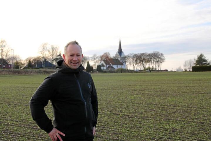 Lars Ole Klavestad ved Råde kyrkje i Østfold. Ho ligg ganske typisk til i kulturlandskapet, og har framleis åkrar og luft rundt seg. Råde kyrkje er ei av få middelalderkyrkjer som har det opprinnelege tårnet. Foto: Janne Grete Aspen
