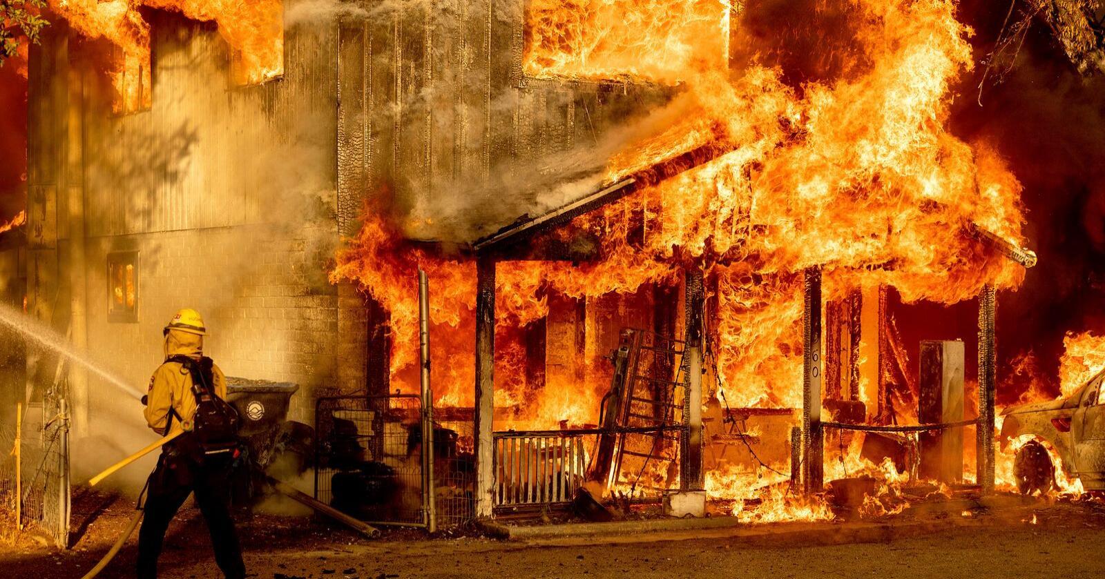 Brannmannskap forsøker å slukke en brann som har spredt seg til bebyggelse i Doyle i California. Foto: Noah Berger / AP / NTB