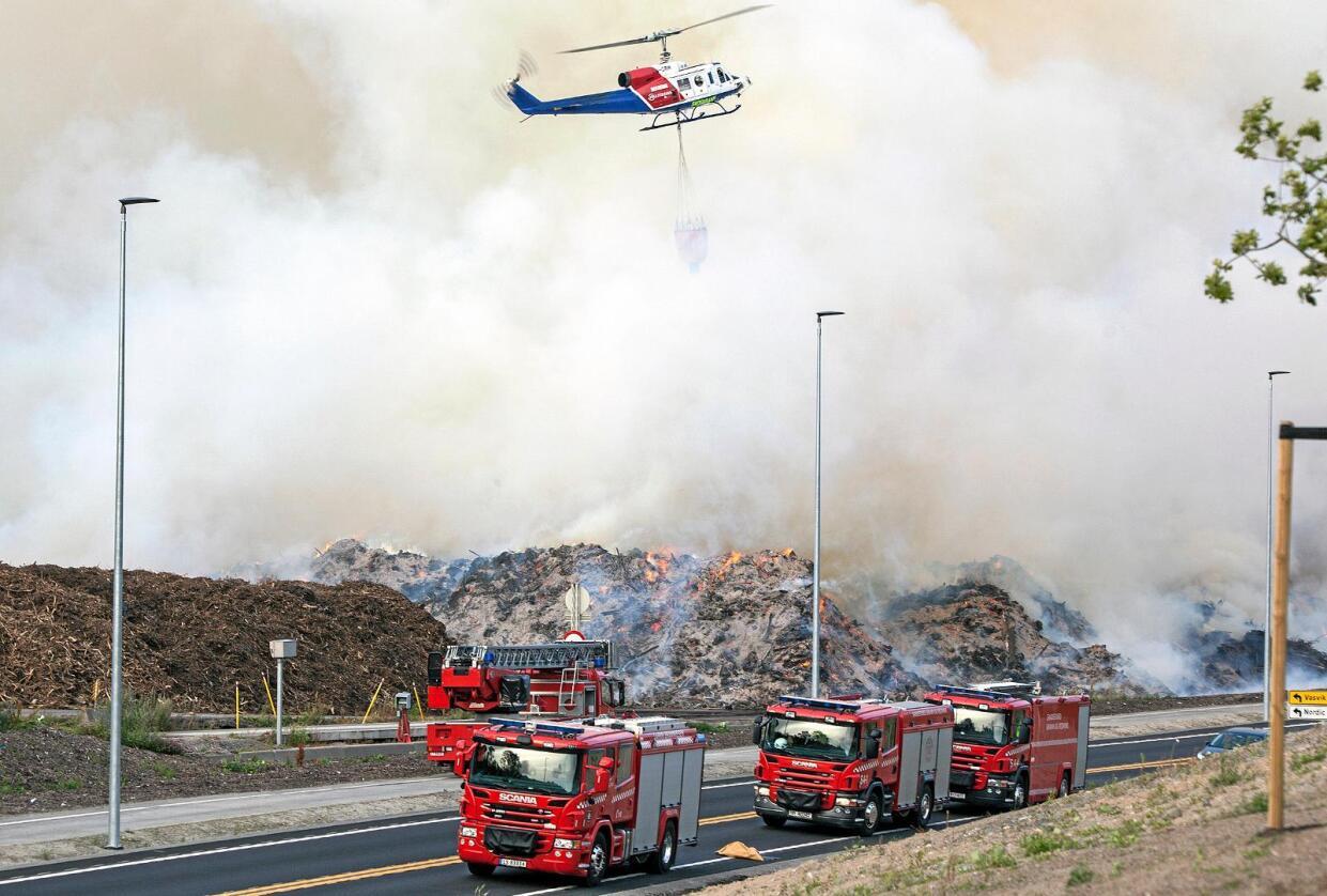 Brannvesenet setter inn helikopter i slokkingen av en omfattende ulmebrann i et barkanlegg på Sky i Larvik. Sterk røykutvikling truer både naboer og trafikk. Foto: Peder Torp Mathisen / NTB scanpix