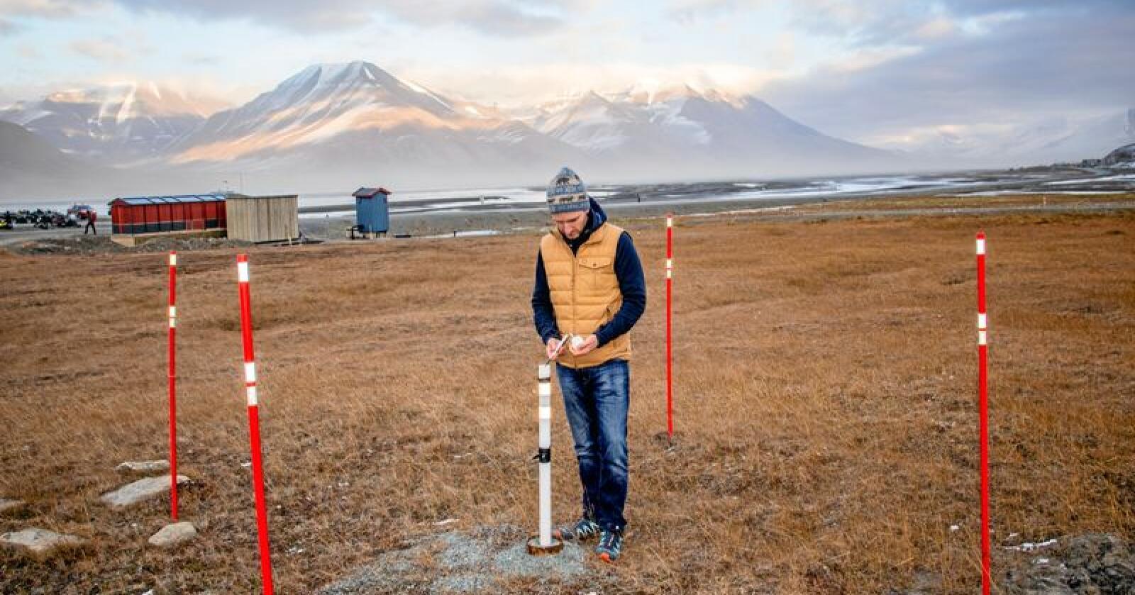Forsker Graham Gilbert måler temperaturen i permafrosten i Longyearbyen på Svalbard. Temperaturmålere er utplassert i borehull i bakken en rekke steder på Svalbard og i andre arktiske områder. Foto: Are Føli / NTB scanpix