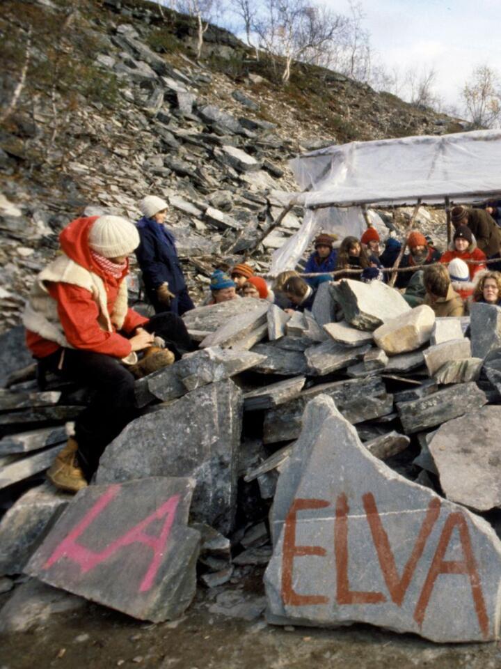 """Finnmarksvidda 1979: Demonstrasjon mot utbyggingen av Alta-Kautokeino-vassdraget. Flere hundre mennesker har slått leir ved nullpunktet i Stilla for å hindre anleggsarbeidet  og kraftutbyggingen. Parolen """"La elva leve"""" er malt på steiner. Foto Erik Thorberg / NTB/ NPK"""