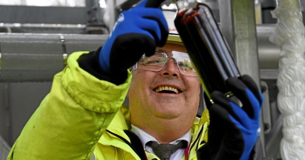Den første olje: Olje- og energiminister Kjell-Bjørge Freiberg holder her opp den første oljen som kommer fra Johan Sverdrip-feltet til Mongstad-anlegget. Foto: Marit Hommedal / NTB scanpix