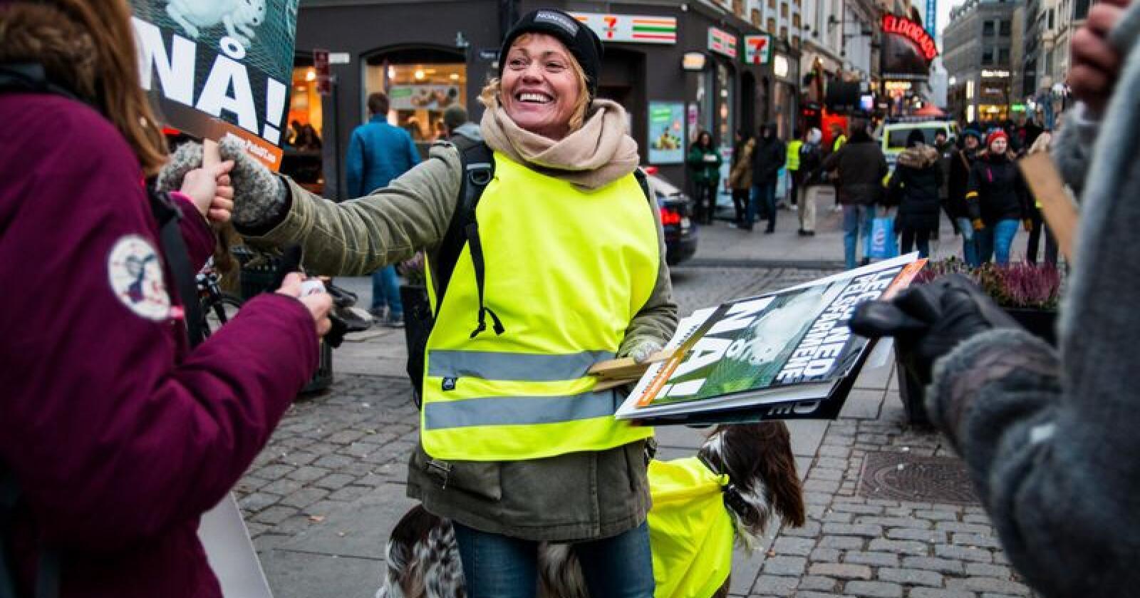 """Dette bilete viser Aina Winsvold som under Noah sitt fakkeltog mot pels deler ut plakatar med påskrifta """"Legg ned pelsdyrfarmene nå"""".  Det blei tatt på Youngstorget i Oslo i oktober 2018. Foto: Maren Kalleberg"""