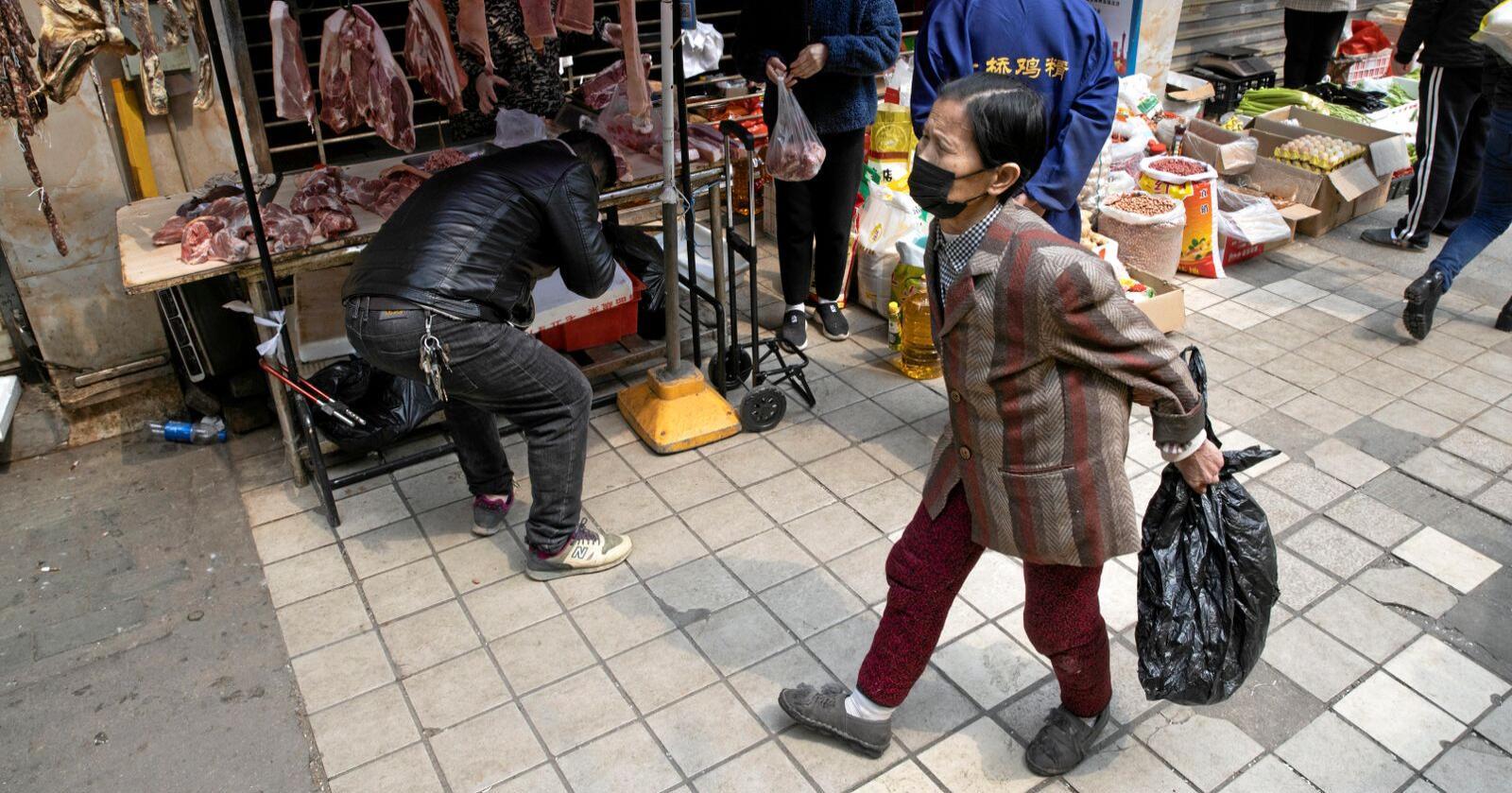 Lokale beboere går forbi en salgsbod i det delvis avstengte markedet i Wuhan i Kina. WHO mener myndighetene bør vektlegge hygienetiltak og at markedene kan fortsette å holde åpent. Foto: Ng Han Guan / AP / NTB scanpix