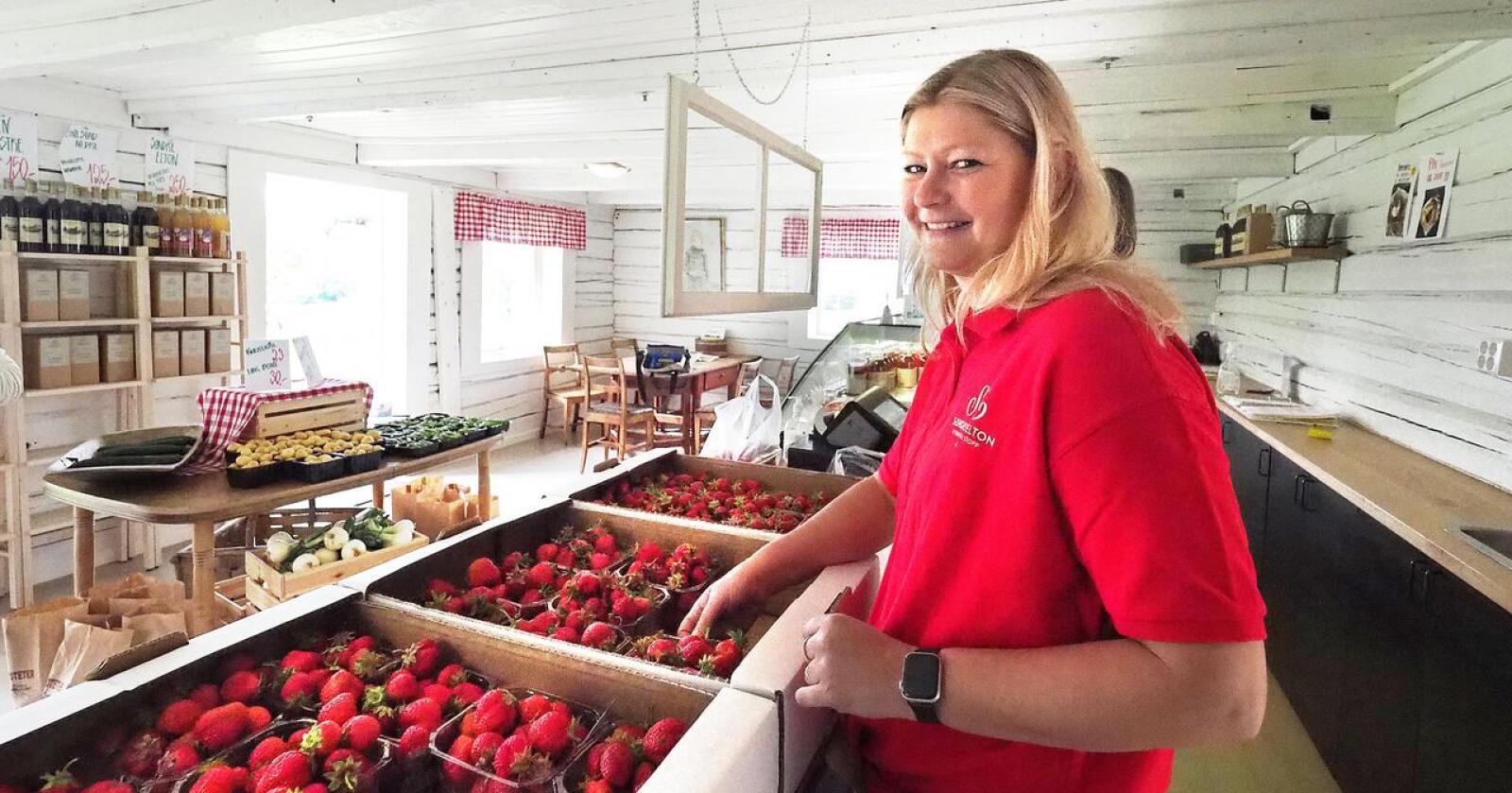 Anette Løvlien Vold selger bær inne i jordbærkiosken de driver på gården. Foto: Siri Juell Rasmussen