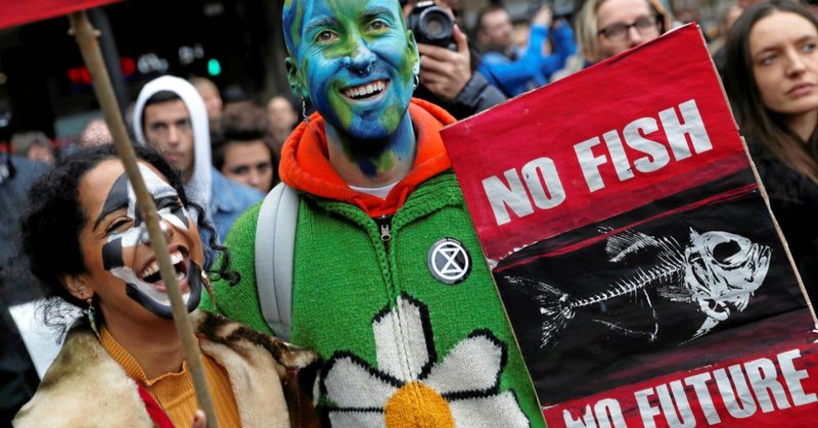 """""""Ingen fisk, ingen fremtid"""" står det på plakatene til disse klimademonstrantene i London på mandag. Nationen har ingen spesiell grunn til å anta at noen av demonstrantene på bildet var blant de arresterte. Foto: Alastair Grant / AP / NTB Scanpix"""