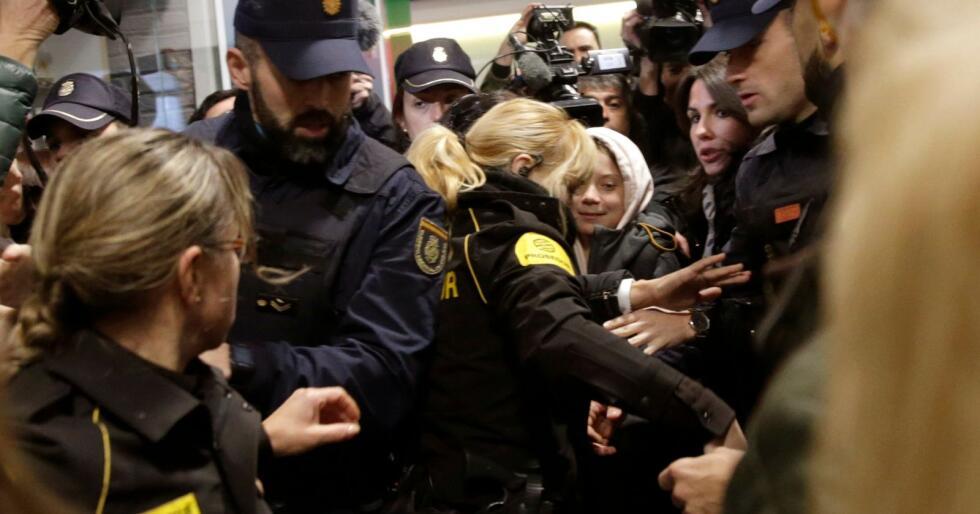 Greta Thunberg eskorteres gjennom togstasjonen i Madrid fredag morgen etter å ha tatt nattoget fra Lisboa. Hun ble møtt av et stort pressekorps og mange andre skuelystne, og det var til tider trengsel på stasjonen. Foto: AP / NTB scanpix